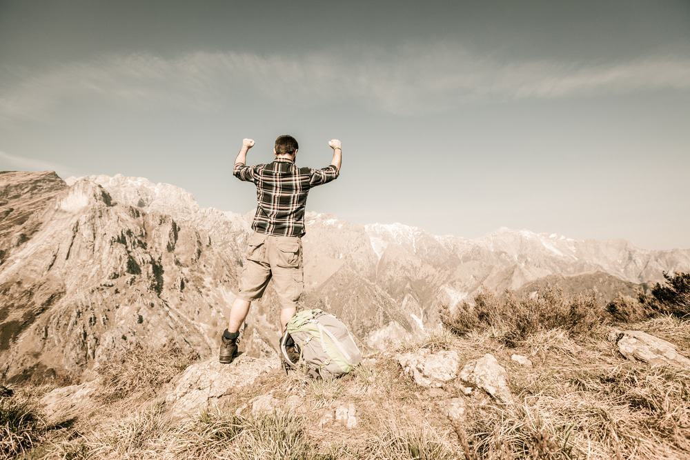 Happy Young Man at Top of the Mountain
