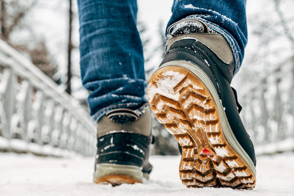 Walking in the snow. Closeup of winter shoes