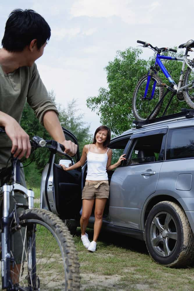 Man on a bike turning to look at woman standing next to car