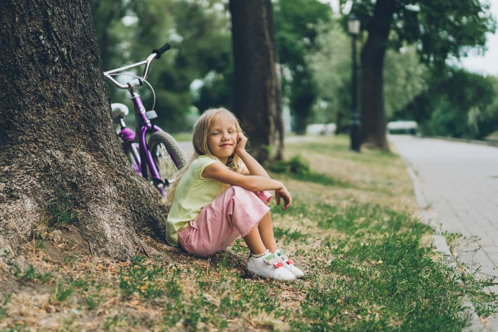 Side view of adorable smiling kid resting near bicycle under tree in park