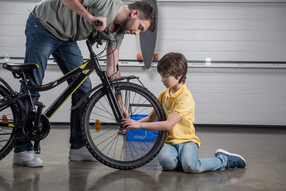Side view of father and little son checking tire of bicycle