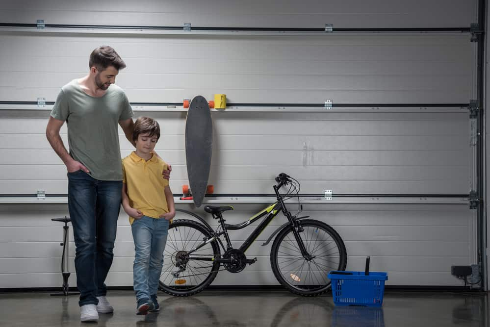 Smiling father and son standing together in workshop with bicycle and skateboard