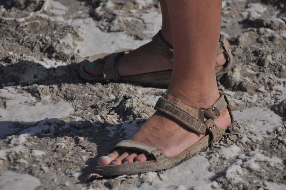 They are walking in sandals on the bottom of a dried and cracked lake Akrotiri in Cyprus.