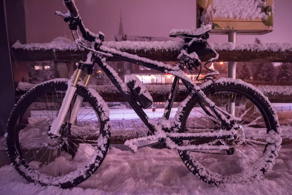 end of biking season.parked bicycle covered by snow from a heavy snowstorm.Winter cycling