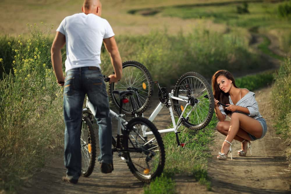 Bicycle has flat tyre and man helps his girlfriend pump it up