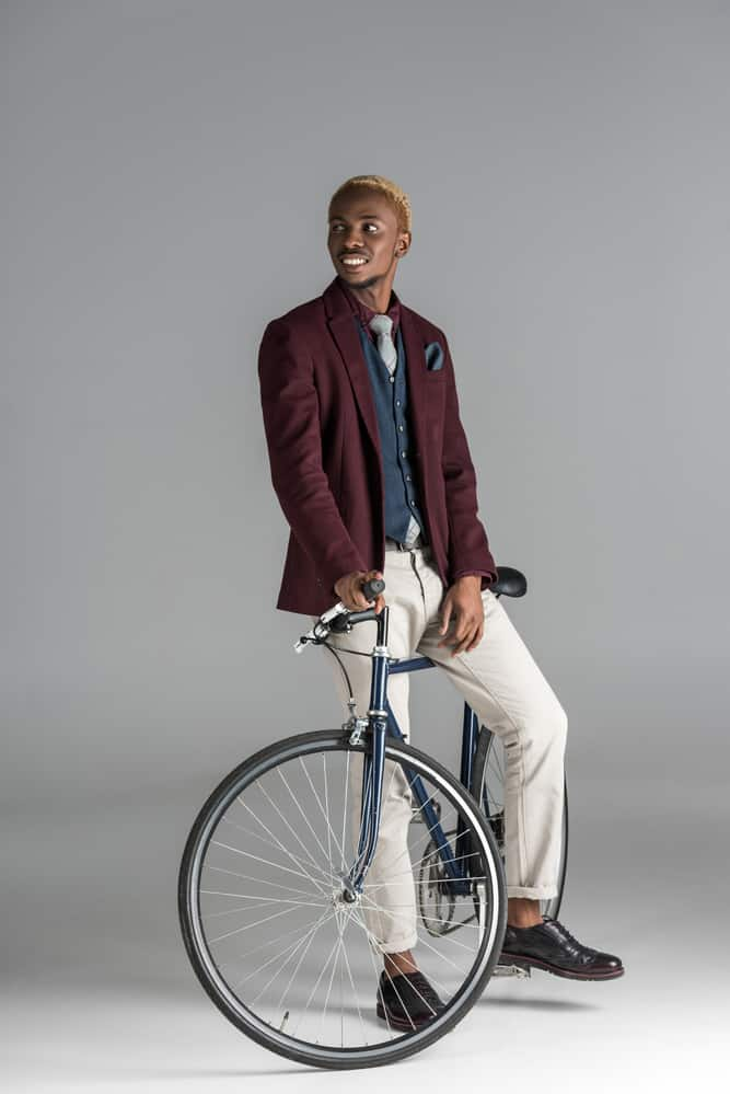 Smiling african man sitting on bike and looking away