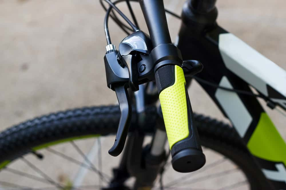 bicycle handlebar with green grips on street background