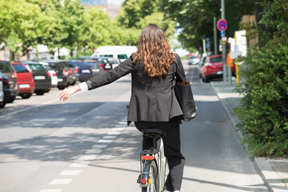 Young Businesswoman Showing Turn On Bicycle