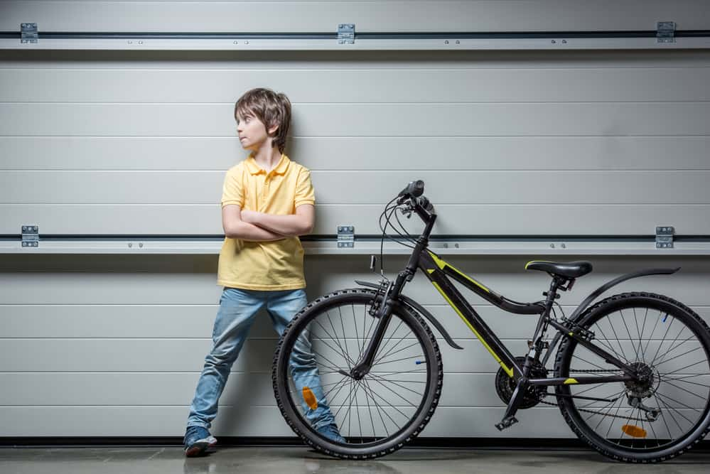 Adorable boy standing at grey wall with mountain bike