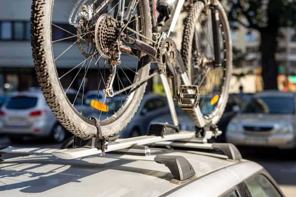 Close-up bicycle on car roof rack railing at outdoor parking. Vehicle with mounted bike on rooftop. Active sport touristic trip concept