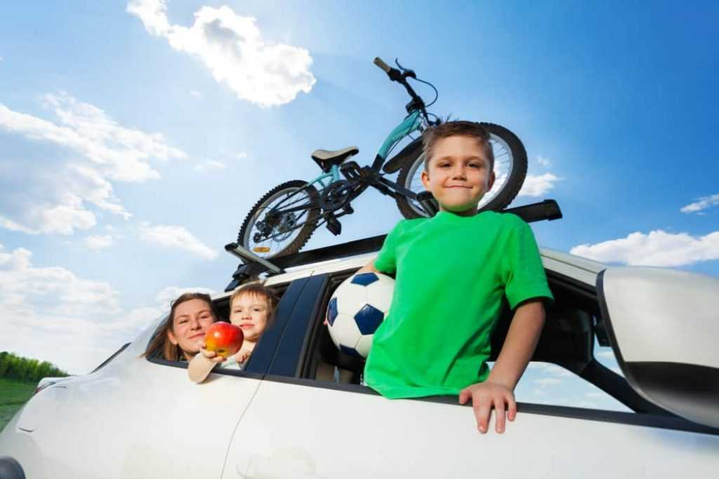 Happy sporty family travelling by car in summer