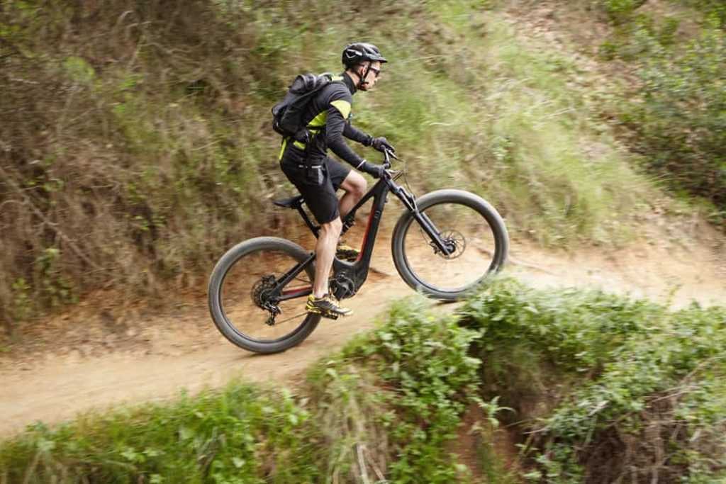 Young Caucasian professional rider performing mountain biking stunts on two-wheeled motor-powered bicycle on trail along cliff using pedal-assist system. Male biker cycling outdoors on electric bike