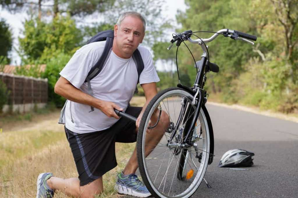 portrait of handsome man pumping bicycle tires at park