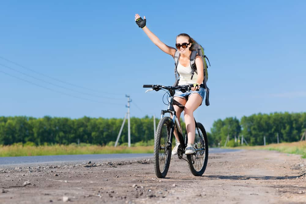 Young pretty woman with backpack riding bicycle outdoors and giving hand signal
