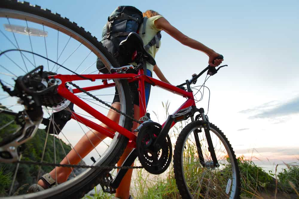 Young woman with backpack and bicycle walking on countryside terrain