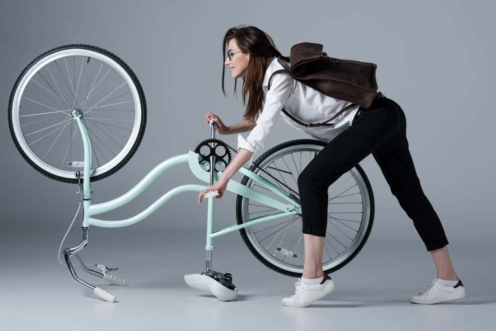 Side view of smiling elegant hipster woman pedaling bicycle by hands